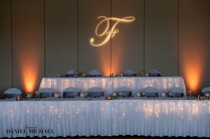 We love the look of this simple head table, with a monogram and uplights.